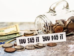 "Image of money next to a tipped over swearing jar. Sign says ""You say it you pay it"""