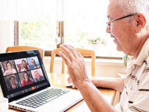 Senior man connecting with his family through a Zoom video conferencing app on his laptop