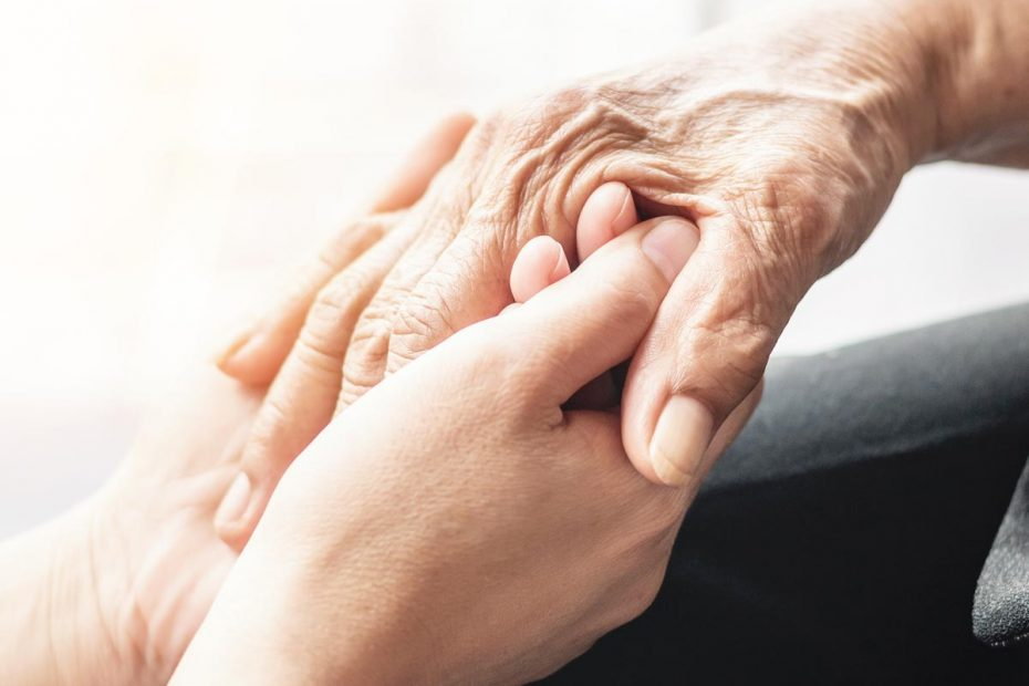 Photograph of young and old hands holding each other