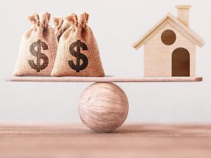 photograph of money sacks balanced on a plank balanced on a ball, with a house on the other end of the plank