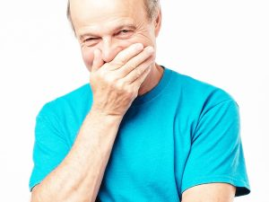 Senior man in a blue t-shirt smirking while covering his mouth with his hand.