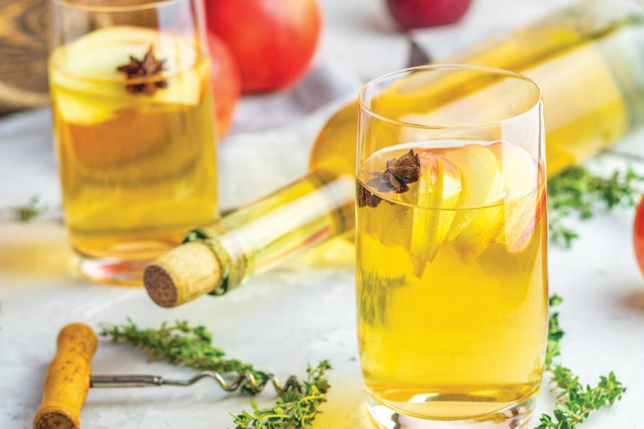 Photograph of hard cider in a corked bottle and in glasses garnished with anise. Apples and herbs in the background.