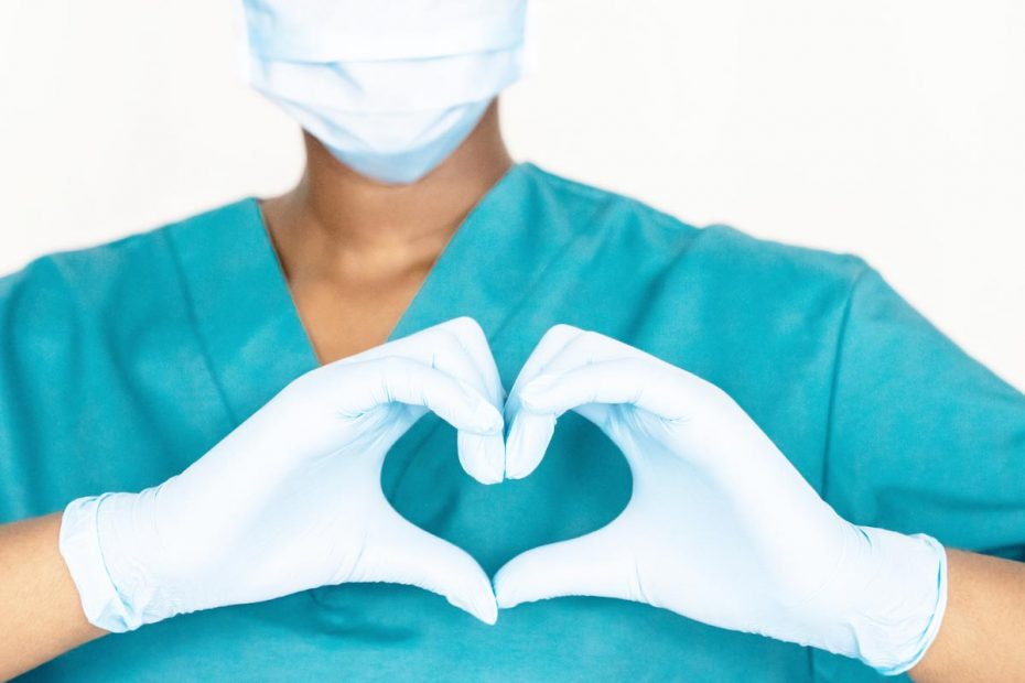 Closely cropped photo of a medical worker making a heart sign with gloved hands