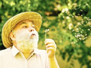 Photo of man in a hat blowing a dandelion, metaphorically representing memories during alzheimer's