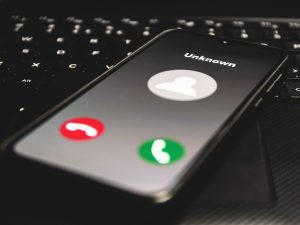 Photo of cell phone featuring a call from an unknown caller