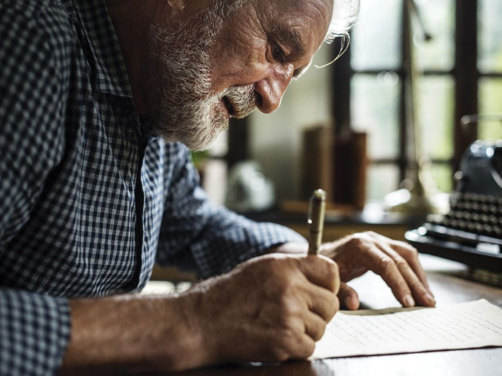 Photo of senior man with beard leaning over and writing on a piece of paper