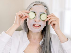 Photo of senior woman doing a skin cleanse, holding up cucumber slices to her eyes