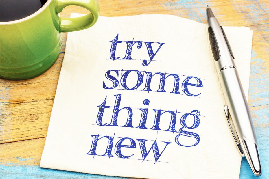 """Photo of green coffee cup with napkin that has """"try something new"""" written on it."""