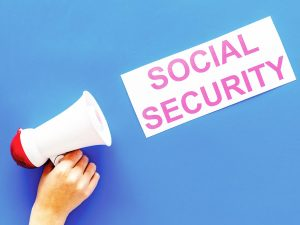 """Senior activist conceptual photo of a hand holding a bullhorn pointed at a sign that reads """"SOCIAL SECURITY"""" on a blue background."""