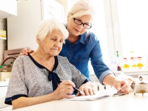 Photo of senior woman standing over her mother, helping her with paperwork.