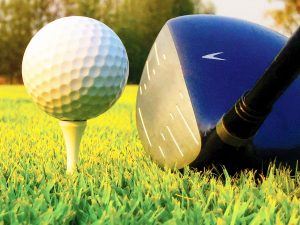 Closeup photo of a driver aiming at a golf ball resting on a tee.
