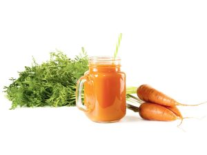 Image of carrots next to a glass of carrot juice