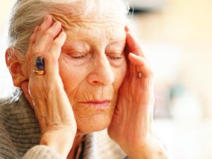Photo of senior woman holding her head from pain
