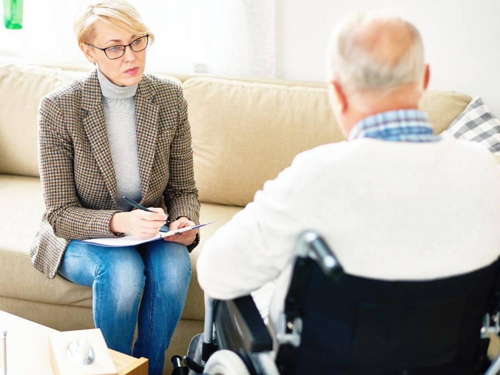 photo of back of senior man in a wheelchair in a session with a female counselor