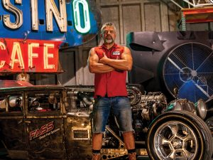 Photo of Steve Darnell originally from Billings, Mont., standing in front of his Rat Rod.
