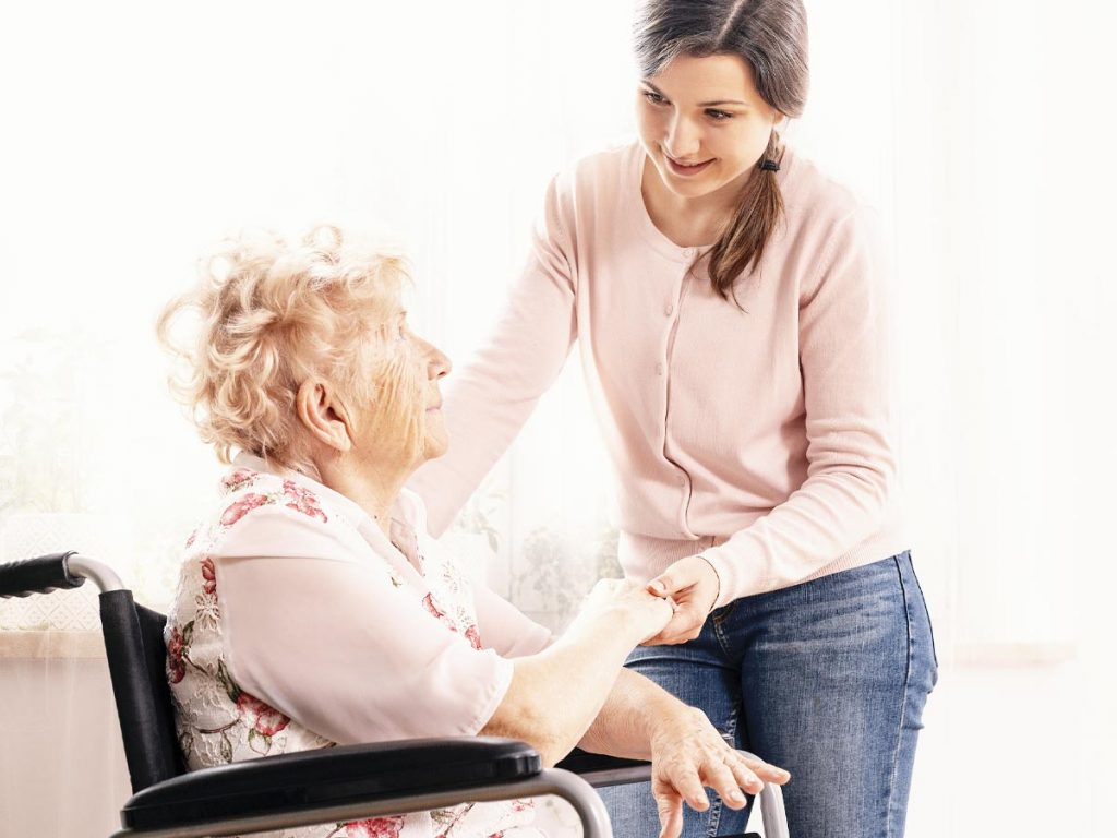 Photo of young woman standing next to a senior woman in a wheelchair.